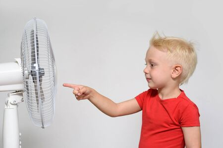 Little blond boy in a red t-shirt touches the fan with his finger. Summer concept 版權商用圖片