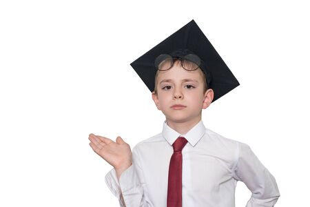 Boy in a square academic hat and glasses holds his palm up. School concept. Isolate