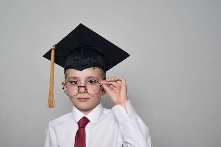 Junge in einer quadratischen akademischen Kappe und einem weißen Hemd, das eine Brille korrigiert. Weißer Hintergrund. Schulkonzept