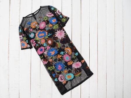 KHARKOV, UKRAINE - APRIL 27, 2019: Black dress in flowers on a white wooden background. Clothing concept. Flat lay 報道画像