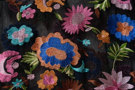 KHARKOV, UKRAINE - APRIL 27, 2019: Bright flowers embroidered on black fabric. Close-up