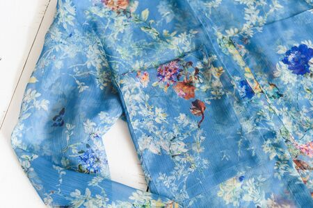 KHARKOV, UKRAINE - APRIL 27, 2019: Details of blue floral blouse. Clothes concept. Wooden background. 報道画像