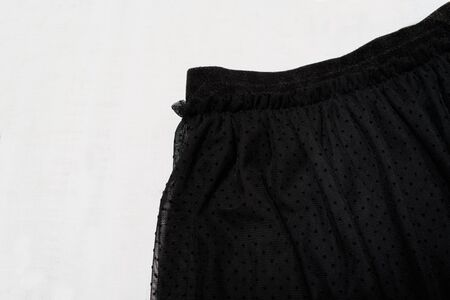 Clothes fashion concept. Detail of black tulle skirt on white wooden background. Top view