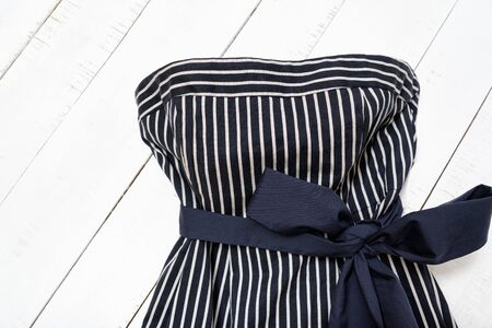 Clothes fashion concept. Detail of blue striped dress with bow on white wooden background. Top view