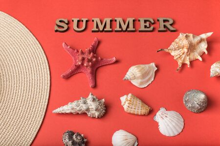 Word Summer from wooden letters. Seashells, part of a hat and a live coral background. Flat lay. Marine concept Фото со стока