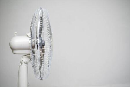 Floor fan standing on a gray wall background. Reklamní fotografie - 128366241