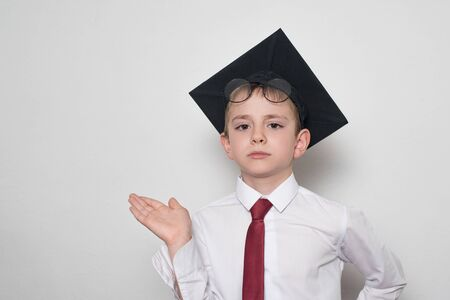 Boy in a square academic hat and glasses holds his palm up. School concept. White background.