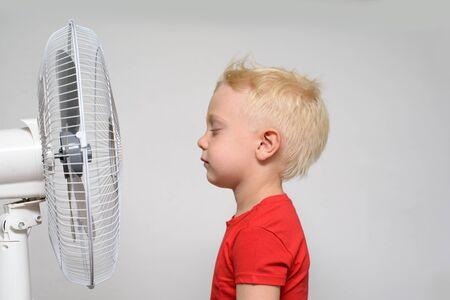 Hübscher lächelnder blonder Junge im roten Hemd und geschlossenen Augen, die die kühle Luft genießen. Sommerkonzept Standard-Bild