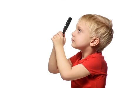 Ragazzo biondo con una lente d'ingrandimento nelle sue mani. Piccolo esploratore. sfondo bianco