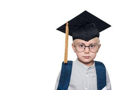 Porträt eines süßen blonden Jungen in großen Gläsern, akademischem Hut und Schultasche. Weißer Hintergrund. Platz für Text