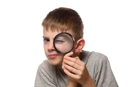 Boy with a magnifying glass in his hands. Little explorer. White background