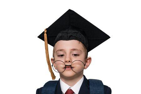 Divertido retrato de un colegial con un sombrero académico y gafas grandes. Aislar. Concepto de escuela Foto de archivo