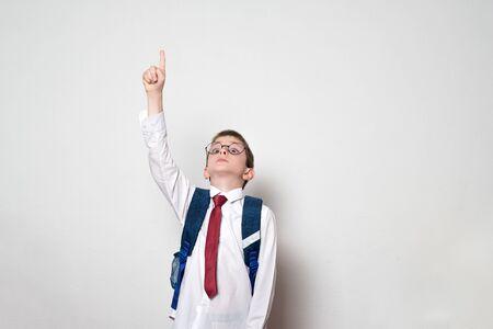 Junge mit Rucksack und runder Brille zeigt mit dem Finger nach oben. Schulkonzept. Weißer Hintergrund. Standard-Bild