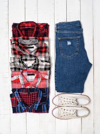 Clothing concept. Plaid shirts, blue jeans and white sneakers on a white wooden background. Top view