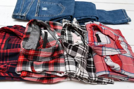 Plaid shirts and blue jeans on a white wooden background. clothing concept.