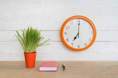 Round wall clock, pink notepad on the table and green houseplant. Workplace. Begining of the work day