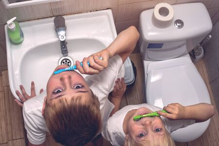 Two boys brushing their teeth in the bathroom. Morning hygiene. Top view Stock Photo