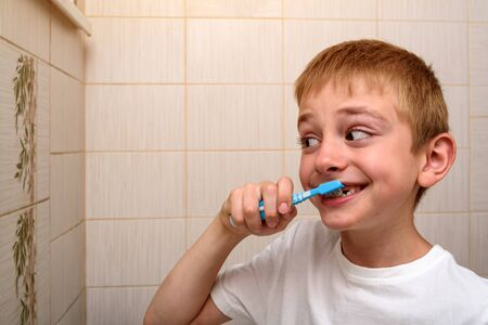 Smiling schoolboy diligently brushes his teeth in the bathroom. Healthy habits
