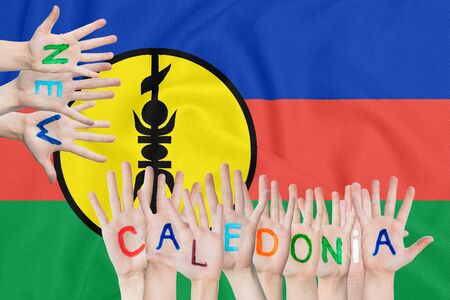 Inscription New Caledonia on the childrens hands against the background of a waving flag of the New Caledonia