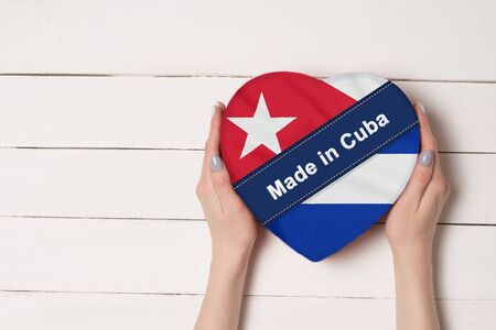 Inscription Made in Cuba, the flag of Cuba. Female hands holding a heart shaped box. White wooden table on a background. Place for text 写真素材