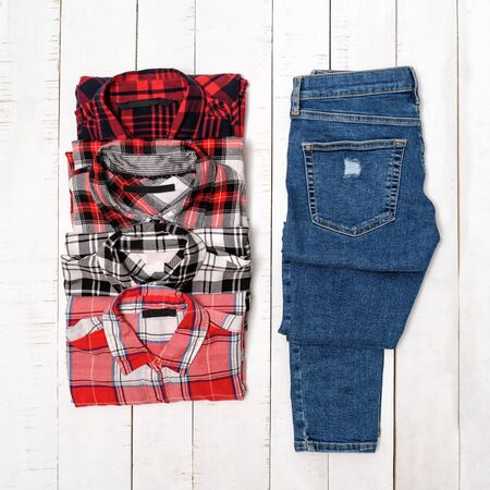 Four plaid shirts and blue jeans on a white wooden background. Clothing concept. Top view