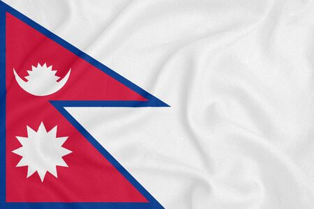 Flag of Nepal on textured fabric. Patriotic symbol Фото со стока