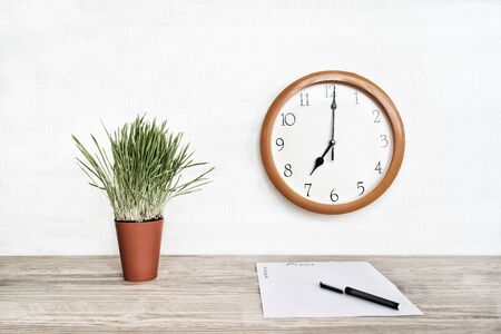 Round clock on a white wall, green houseplant and a blank sheet of paper with a pen. Business planning Stockfoto