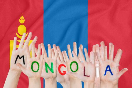 Inscription Mongolia on the childrens hands against the background of a waving flag of the Mongolia