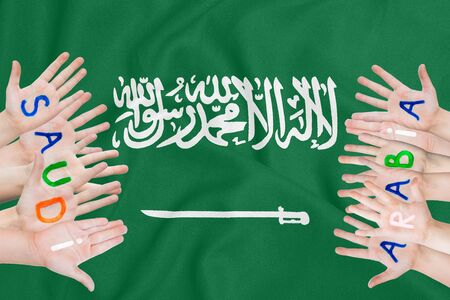 Inscription Saudi Arabia on the childrens hands against the background of a waving flag of the Saudi Arabia Stock fotó