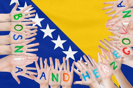 Inscription Bosnia and Herzegovina on the childrens hands against the background of a waving flag of the Bosnia and Herzegovina