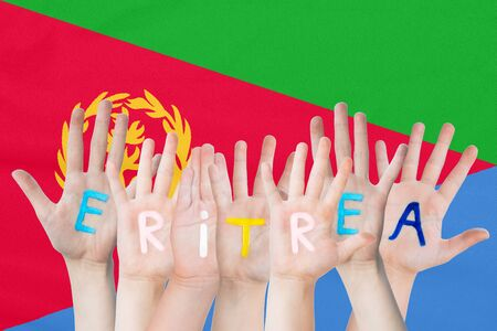 Inscription Eritrea on the childrens hands against the background of a waving flag of the Eritrea