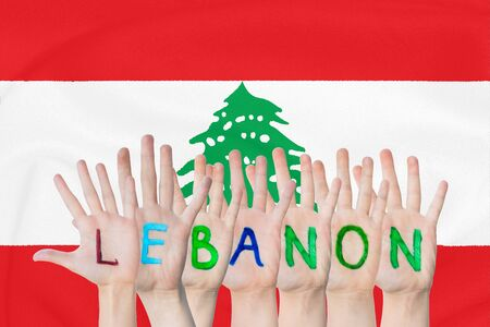 Inscription Lebanon on the childrens hands against the background of a waving flag of the Lebanon Stockfoto