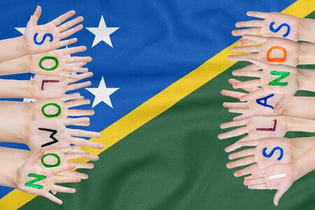 Inscription Solomon Islands on the childrens hands against the background of a waving flag of the Solomon Islands