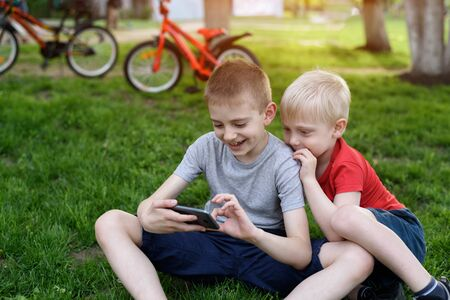 Two boys are gaming on the smartphone while sitting on the grass. Bicycles in the background 写真素材