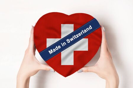 Inscription Made in Switzerland the flag of Switzerland. Female hands holding a heart shaped box. White background.