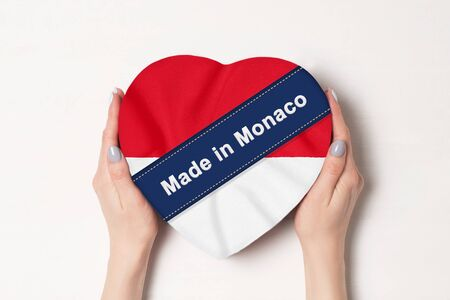 Inscription Made in Monaco the flag of Monaco. Female hands holding a heart shaped box. White background.