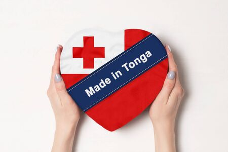 Inscription Made in Tonga the flag of Tonga . Female hands holding a heart shaped box. White background.