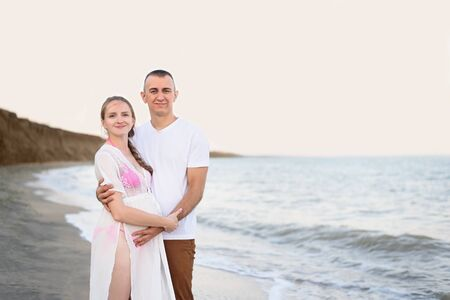 Young married couple on the sea coast. Husband hugs his pregnant wife. Pre-sunset time