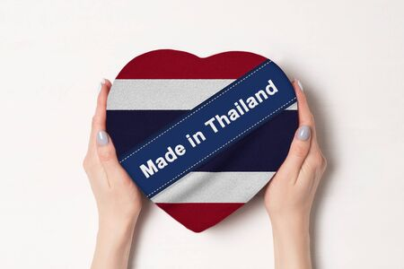 Inscription Made in Thailand the flag of Thailand. Female hands holding a heart shaped box. White background. Stock fotó