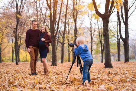 Little blond boy with a big SLR camera on a tripod. Photographs a married couple, pregnancy. Family photo session