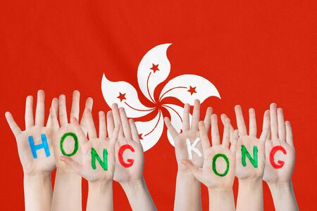 Inscription Hong Kong on the childrens hands against the background of a waving flag of the Hong Kong