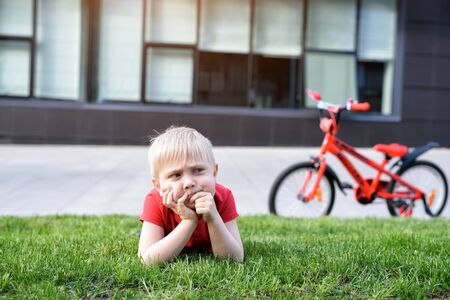 Pensive blond boy is resting on the lawn. Bike in the background 写真素材