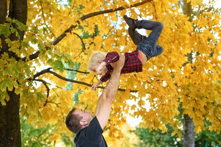 Father throws up his blond son. Yellow leaves on background. Family concept