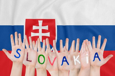 Inscription Slovakia on the childrens hands against the background of a waving flag of the Slovakia
