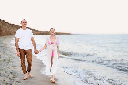 Young married couple walks along the sea coast. Pregnancy. Pre-sunset time Banco de Imagens