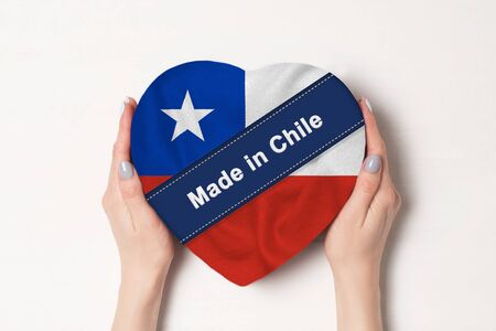 Inscription Made in Chile the flag of Chile. Female hands holding a heart shaped box. White background.