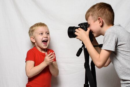 Joy boys are photographing each other with a SLR camera. Home studio. Young blogger. White background