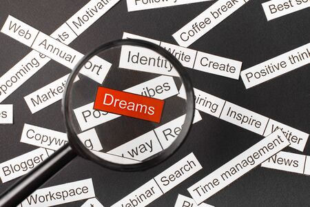 Magnifier glass over the red inscription dreams cut out of paper. Surrounded by other inscriptions on a dark background. Word cloud concept.