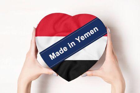 Inscription Made in Yemen the flag of Yemen. Female hands holding a heart shaped box. White background.