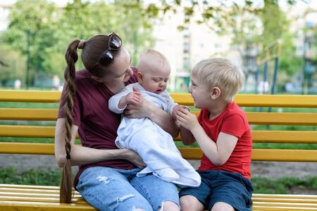 Young mother and two children on a bench in the park. Baby and blond elder brother playing. Spring warm day